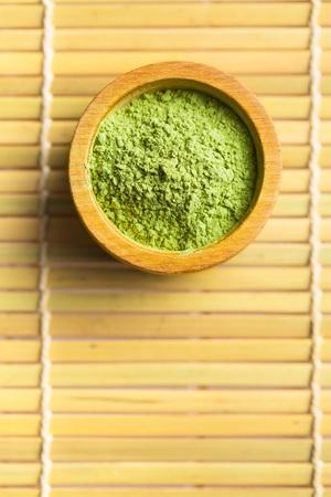 Green matcha tea powder in bowl. Stock Photo