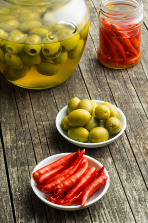 Pickled chili peppers and green olives in bowl. Stock Photo