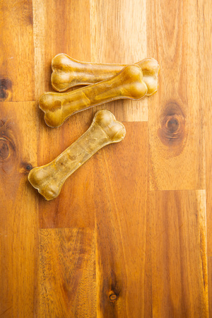 Dog chew bone on wooden table.