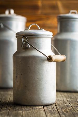 steel. milk: Aluminium milk can on old wooden table.