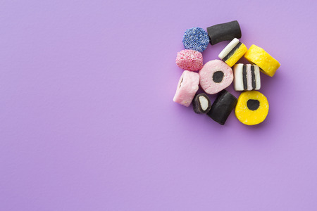 liquorice: Mixed liquorice candies on colorful background. Top view.