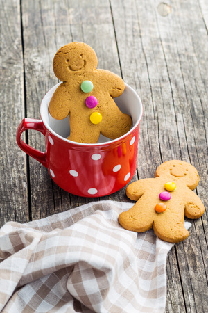Gingerbread man in mug on old wooden table. Stock Photo