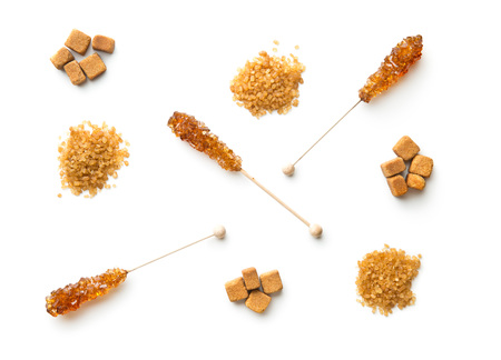 Brown cane sugar, cube sugar and crystalic sugar on wooden sticks isolated on white background. Top view.