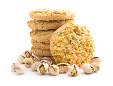 Sweet pistachio cookies and pistachio nuts isolated on white background. Reklamní fotografie