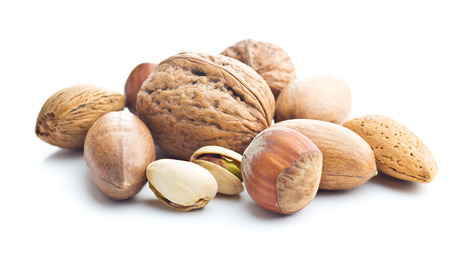 Different types of nuts in the nutshell. Hazelnuts, walnuts, almonds, pecan nuts and pistachio nuts isolated on white background. Imagens