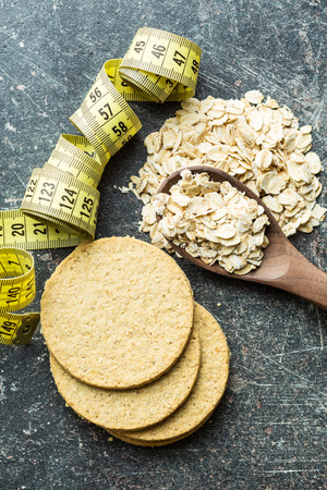 Oatmeal cookies and oat flakes. Diet concept with measuring tape. Stock Photo
