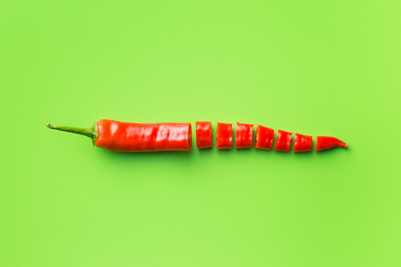 Red chili peppers on green background. Top view. Stock Photo