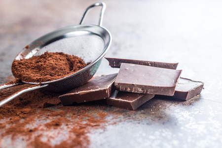 Dark cocoa powder in a sieve and chocolate on old kitchen table. Stock Photo