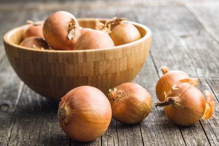 Fresh onion bulbs on old wooden table.