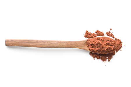 Dark cocoa powder in wooden spoon isolated on white background.