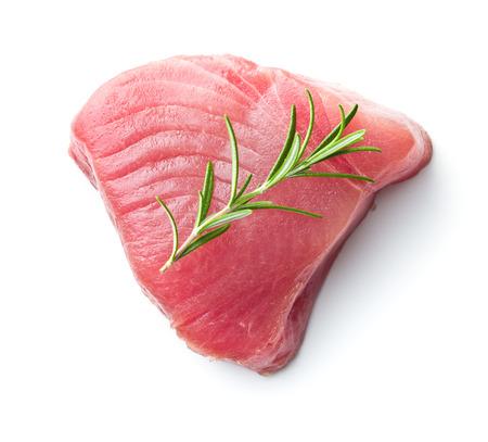 Vers ruw tonijnlapje vlees en rozemarijn die op witte achtergrond wordt geïsoleerd.