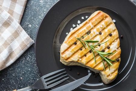Grilled tuna steak on plate.