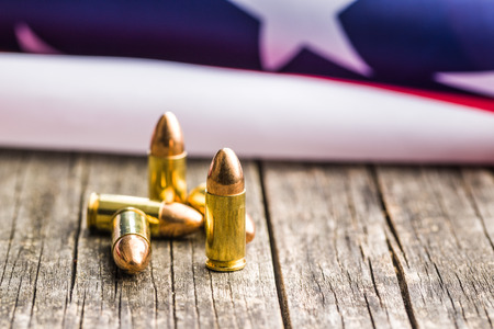 9mm ammo: Pistol bullet and USA flag on old wooden table.