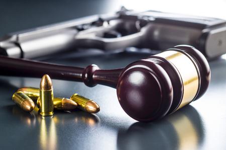 Judge gavel and gun bullets on black table.