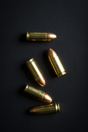9mm pistol bullets on black table.