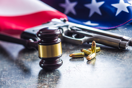 Judge gavel and gun bullets before usa flag.