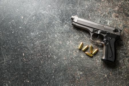 9 ミリメートル ピストルの弾丸と黒いテーブルの上の拳銃。 写真素材