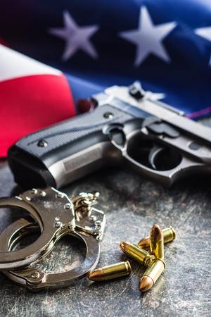 Pistol bullets, handgun and handcuffs on black table.