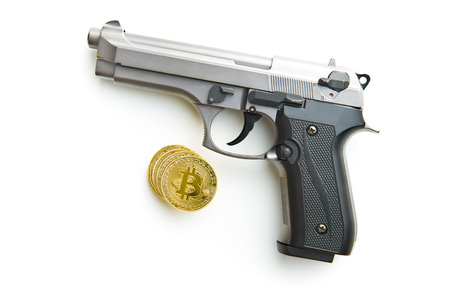 Golden bitcoins. Cryptocurrency and handgun isolated on white background. Stock Photo