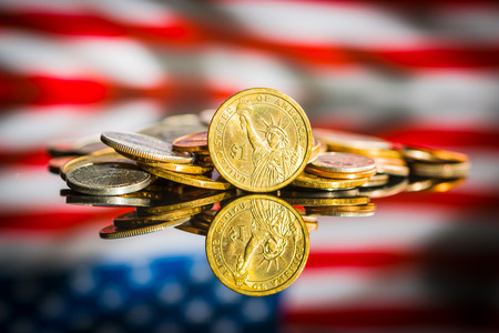 One dollar coin in front of usa flag.