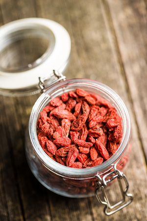 Dried goji berries in jar on old wooden table. Stock Photo