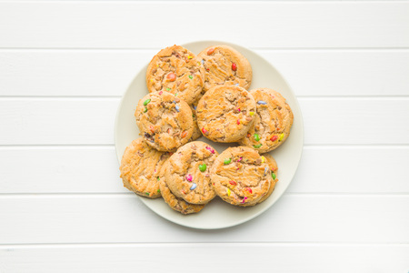 Sweet cookies with colorful candies on white table. Stock Photo