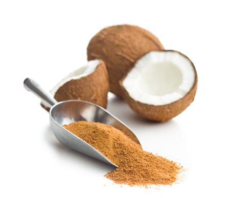 Azúcar dulce del coco en la cucharada aislada en el fondo blanco.