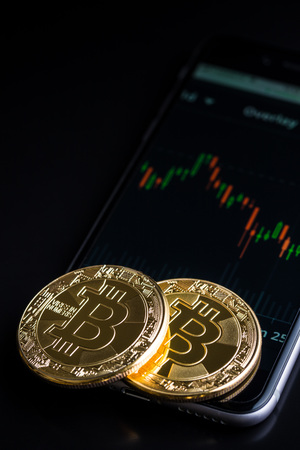 Concept with bitcoins and falling candle graph on cellphone. Stock Photo