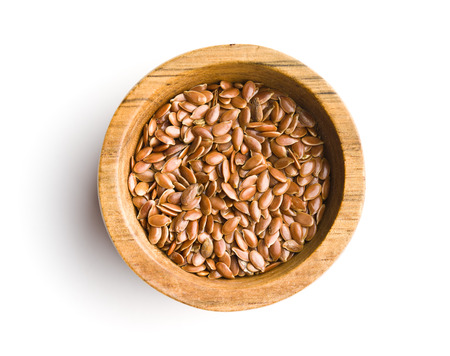 Healthy brown linseeds in bowl isolated on white background.