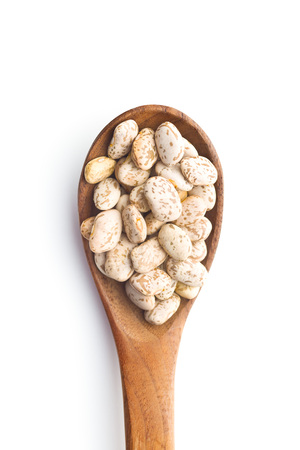 Dried borlotti beans in wooden spoon isolated on white background. Top view.