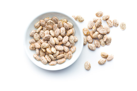 Dried borlotti beans in bowl isolated on white background. Top view.