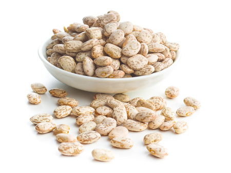 Dried borlotti beans in bowl isolated on white background.