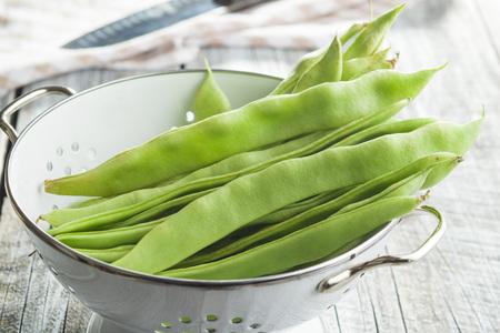 Green string beans pods in colander.
