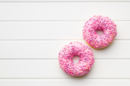 Two pink donuts on white table.