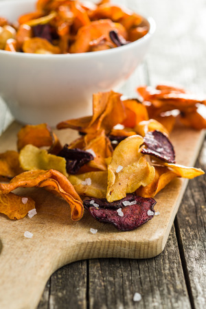 Mixed fried vegetable chips on cutting board.