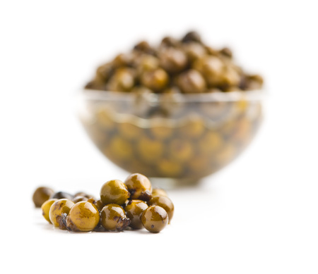 Green peppercorn in brine isolated on white background.