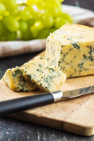 Tasty blue cheese on cutting board.