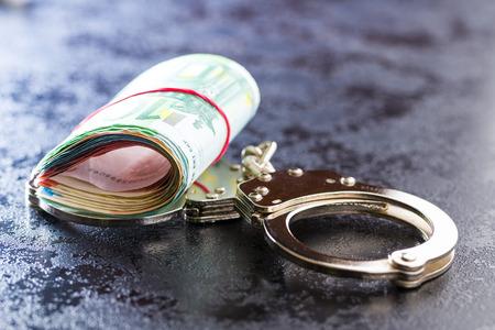 Handcuffs and euro money. Euro banknotes.