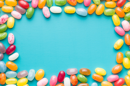 Sweet jelly beans on blue background.