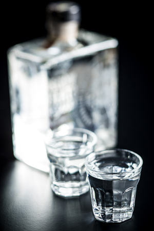Vodka in shot glass. Transparent alcohol on black table.