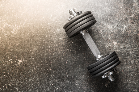 Dumbbell with black weight on grunge background.