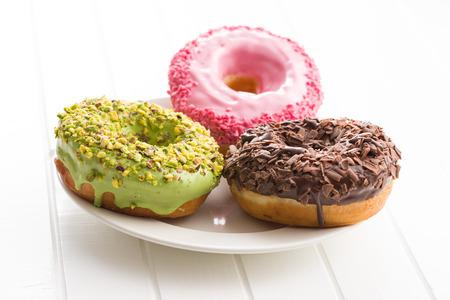 Drei süße Donuts auf dem Teller. Standard-Bild