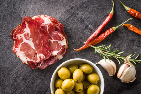 Dried pork meat slices, olives, rosemary, garlic and chili peppers. Фото со стока