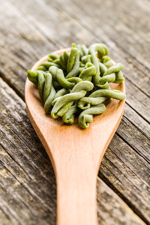 Uncooked spinach gemelli pasta in wooden spoon.
