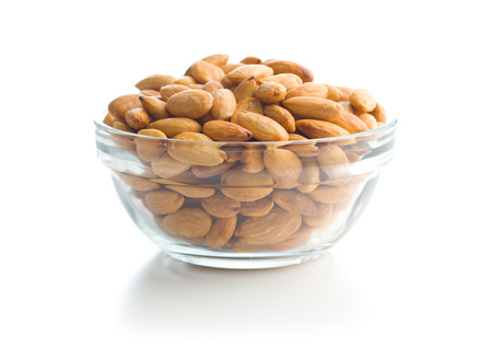 Salty roasted almonds in bowl isolated on white background.