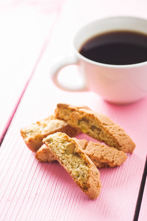 Sweet cantuccini biscuits. Italian biscotti and coffee cup on pink table. Archivio Fotografico