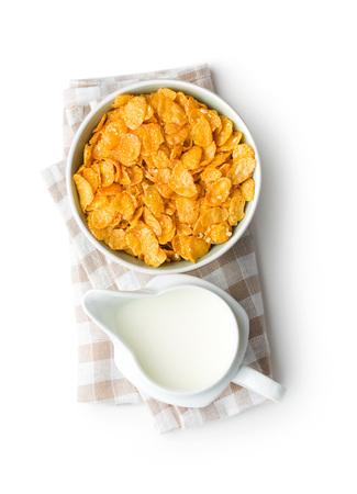 Cereales para el desayuno o copos de maíz en un tazón y leche aislado sobre fondo blanco. Vista superior. Foto de archivo