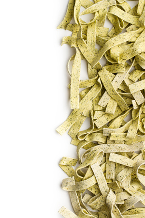 Raw italian pasta. Dry noodles with spinach isolated on white background. Reklamní fotografie