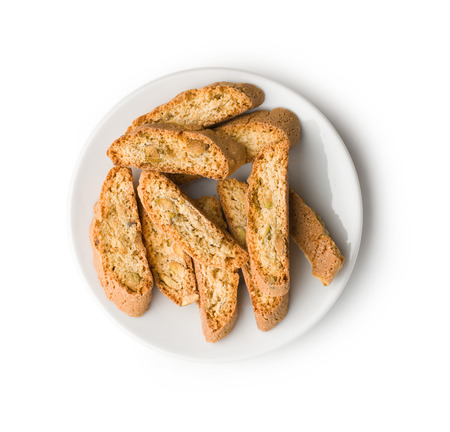 Sweet cantuccini biscuits. Italian biscotti on plate isolated on white background. Top view.