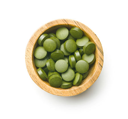 Green chlorella pills or green barley pills in bowl isolated on white background.